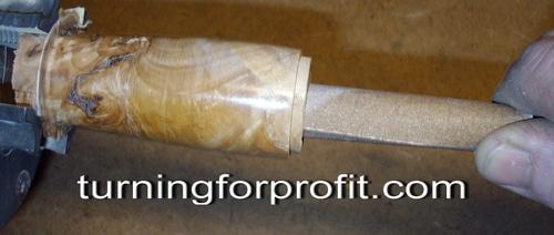 sanding a small wooden art piece